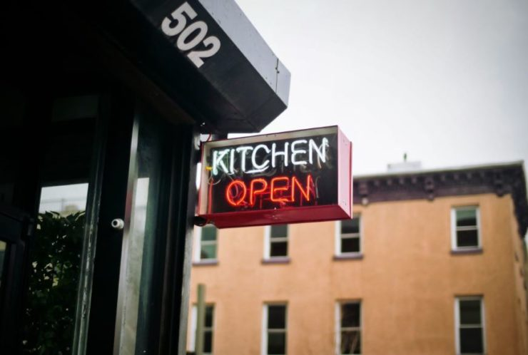 A neon sign that says kitchen open